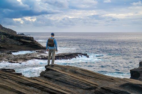 Man in Black Jacket and Blue Denim Jeans Standing on Brown Wooden Dock