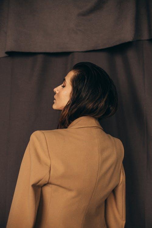 Woman in Brown Blazer Standing Near Brown Curtain