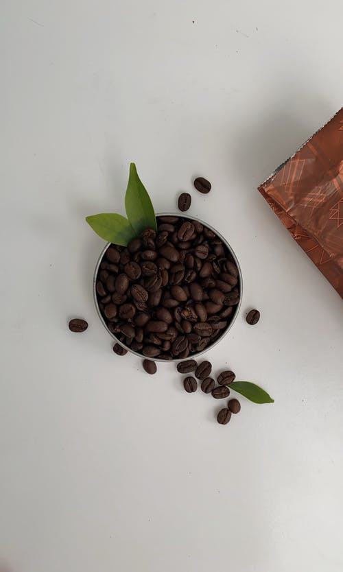 Roasted coffee beans with green leaves on table