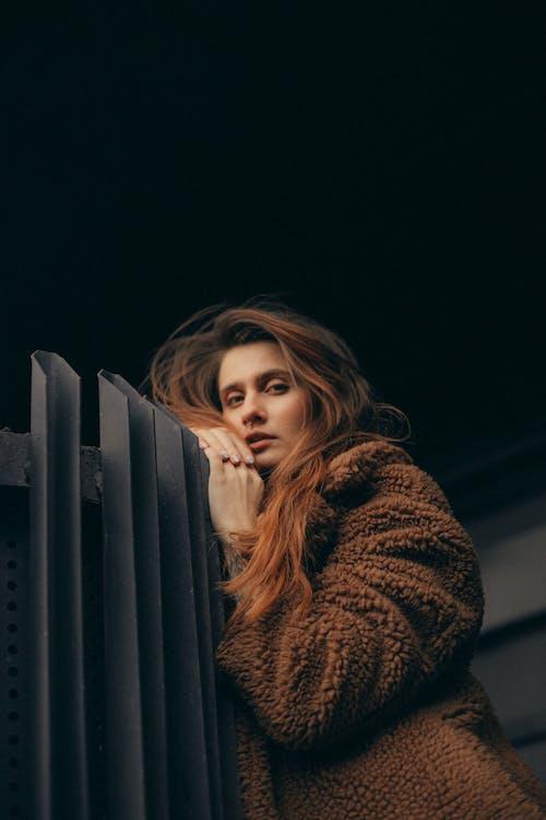 Woman in Brown Fur Coat Standing Beside Black Metal Fence