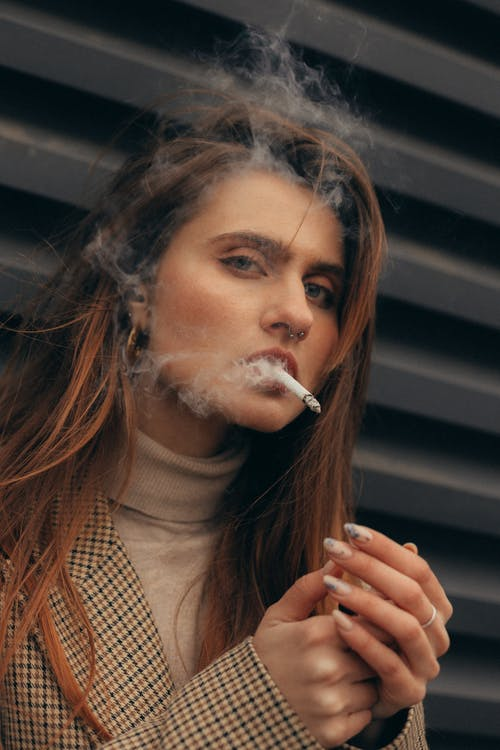 Woman Smoking a Cigarette While Looking at The Camera