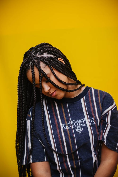 Emotionless ethnic woman with African braids hanging head in studio