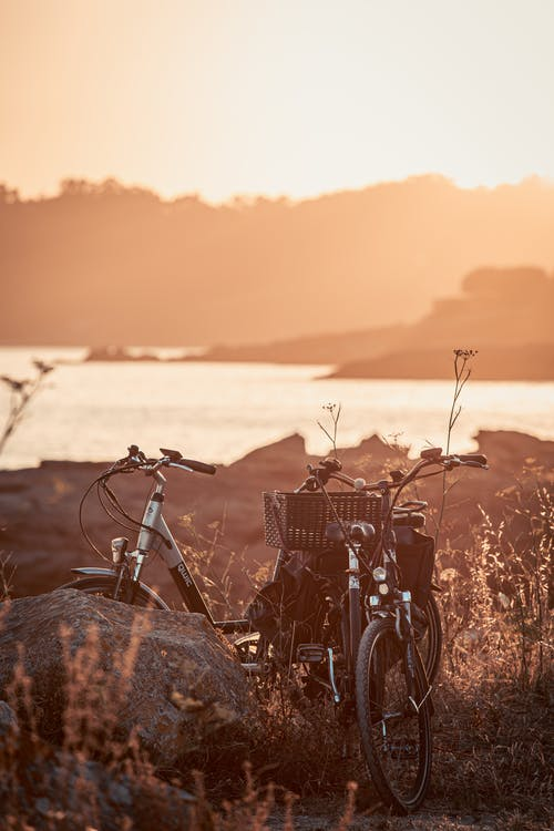 Old bicycles among grass near lake and mountains in evening