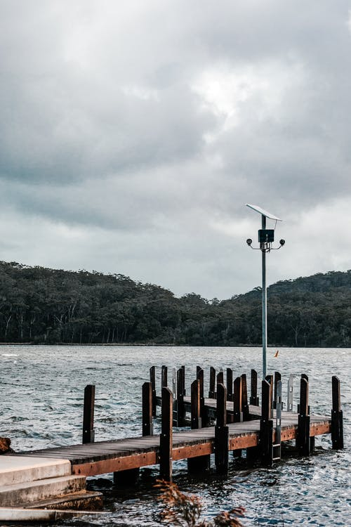 Aged wooden pier with lamp post on rippled ocean against green mount under sky with clouds