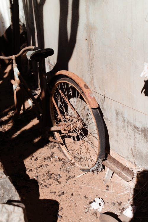 Old fashioned broken rusty bicycle near concrete building