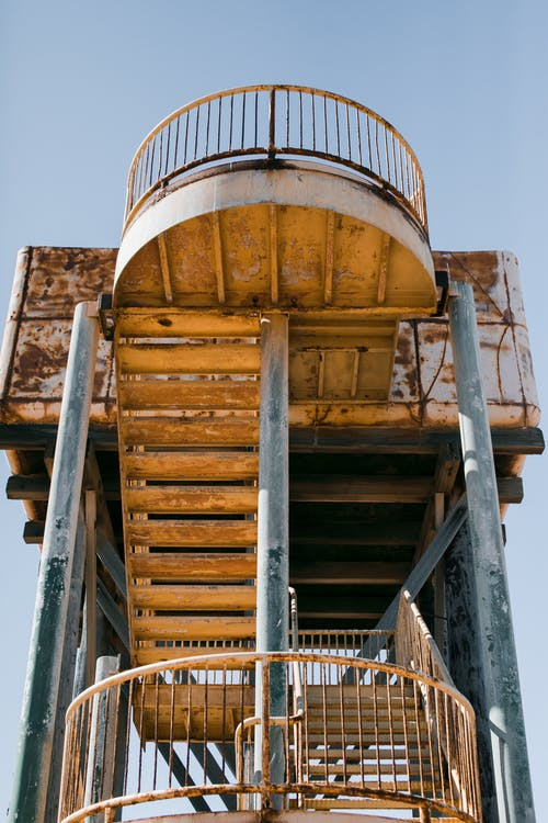 From below of metal stairway with oval railing on metal pillars of shabby building for observing territory