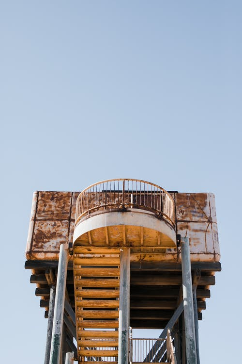 From below of aged rusty abandoned observation tower with stairway against blue cloudless sky