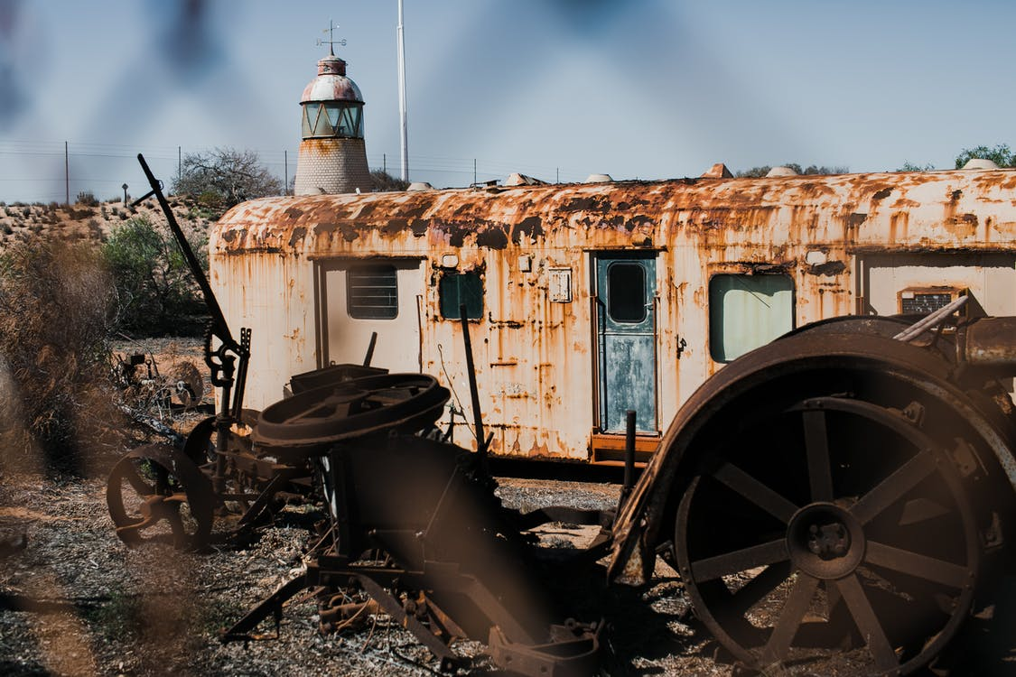 Abandoned rusty wagon and old wheels