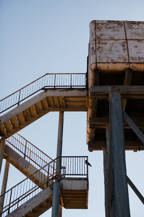 Low angle of tall aged observation tower on tall poles with rusty staircase against clear sky