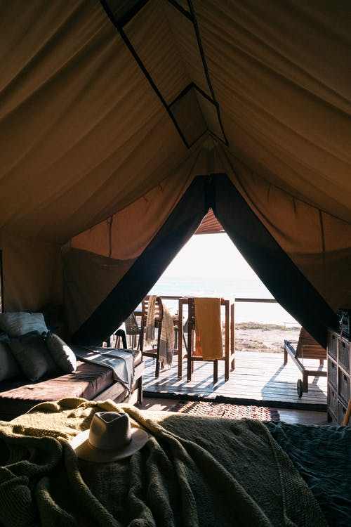 Interior of big tent with beds and lounges outside against sparkling water of sea on beach