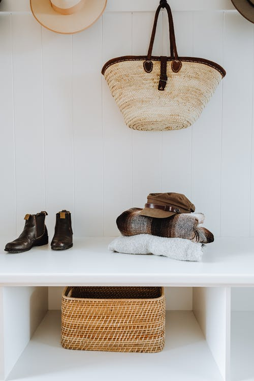 White hallway bench with wicker basket and bag and stylish boots with hats and plaids