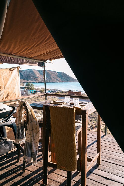 Paved veranda of luxury tent with set table in bright morning sunlight against ocean