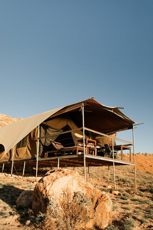 Picturesque view of camping tent located on dry hills under blue cloudless sky in sunny summer day