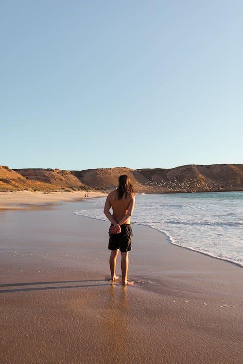 Unrecognizable male admiring sea view on sand