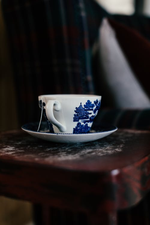 Ceramic white cup with blue pictures standing on saucer on wooden surface in room