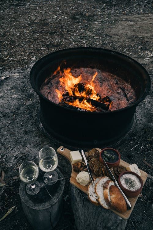 High angle of backyard with bonfire near stumps and with wineglasses and food with knife on cutting board in nature