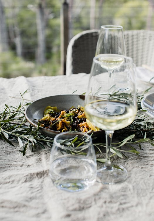 High angle of plate with delicious pasta served on table near glasses with wine and plates and decorated with green plants