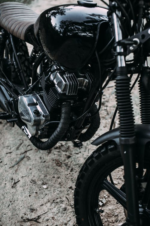Black shiny motorcycle parked on sandy road in summer day in nature outside