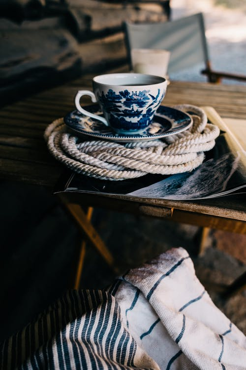 Ceramic cup with saucer filled with tea placed on wicker holder on wooden surface near chair in daylight