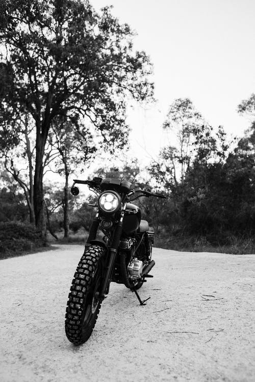 Black and white of motorcycle parked on sandy ground near trees and grass