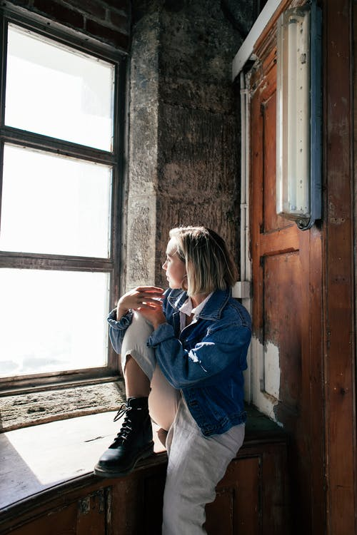 Thoughtful woman sitting in old house