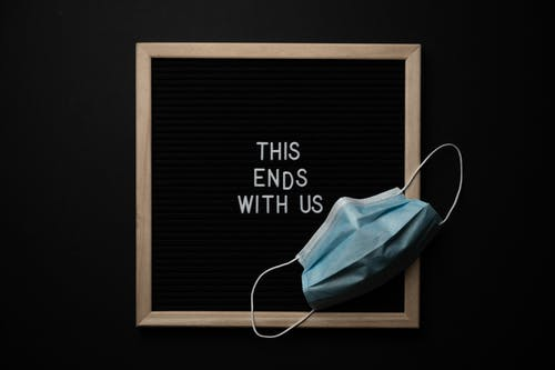From above composition of sterile mask and black chalkboard with THIS ENDS WITH US inscription on black background