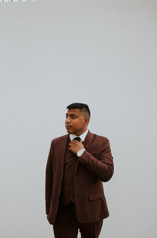 Stylish ethnic male in brown suit standing with hand in pocket and looking away on white background