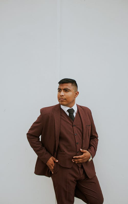 Young ethnic male with short haircut standing with hand in pocket and posing confidently looking seriously