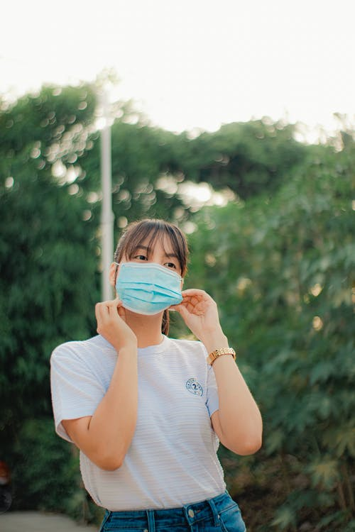 Woman Putting on Face Mask