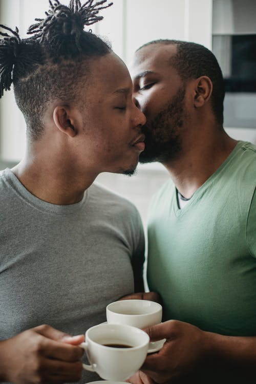 Man Kissing Another Man on the Cheek