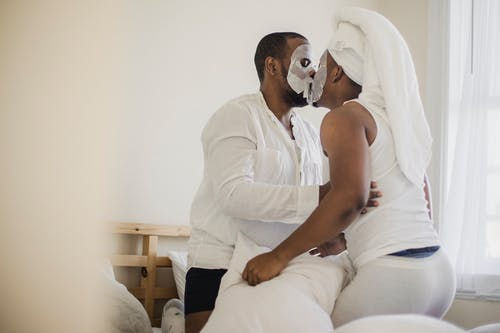 Two Men With Facial Masks Kissing