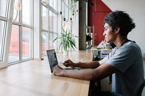 Man in White Crew Neck T-shirt Using Laptop Computer on Brown Wooden Table