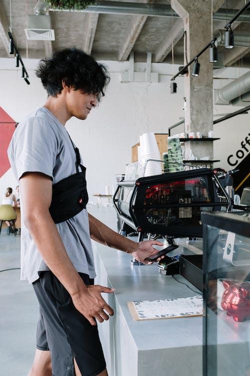 Homme En T Shirt à Col Rond Blanc Et Short Noir Debout Près De La Télévision à écran Plat Noir