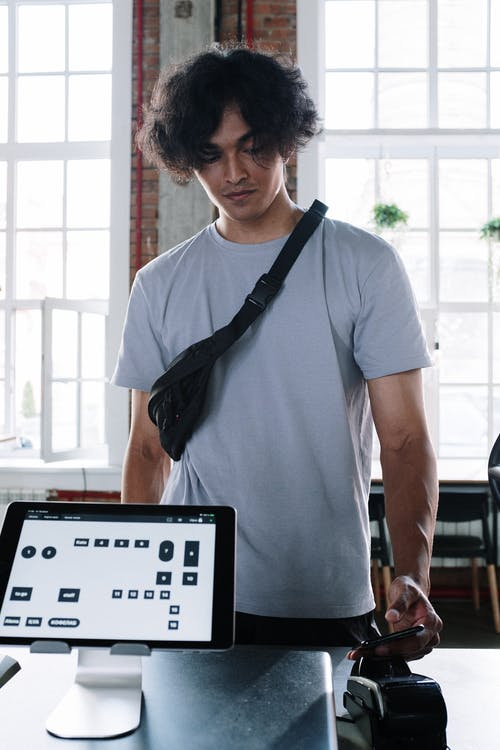 Homme En T Shirt à Col Rond Blanc Debout Près D'un Ordinateur Portable Noir