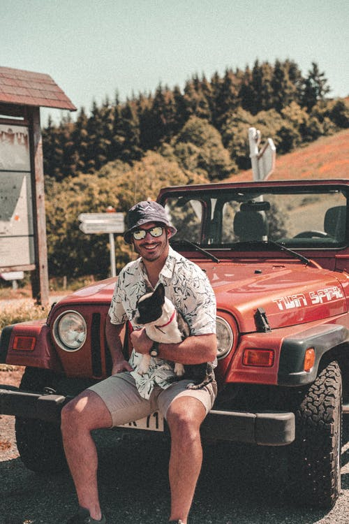 Woman in White and Black Shirt Sitting on Red Jeep Wrangler