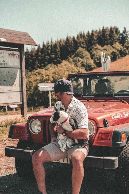 Man in White and Black Crew Neck T-shirt Sitting on Red Jeep Wrangler