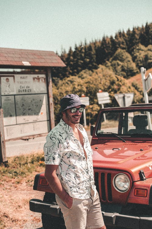 Man in White Green and Black Floral Button Up T-shirt Standing Beside Red Car during