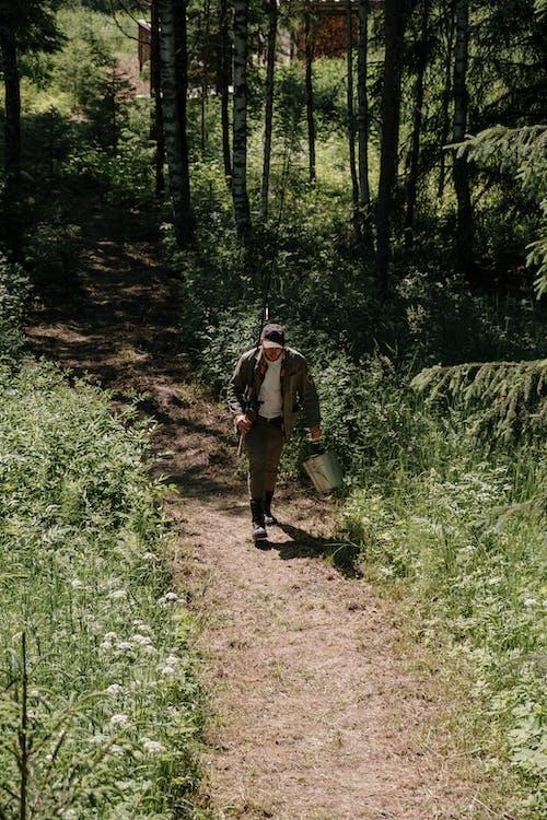 Man in Brown Jacket Walking on Dirt Road Between Green Trees