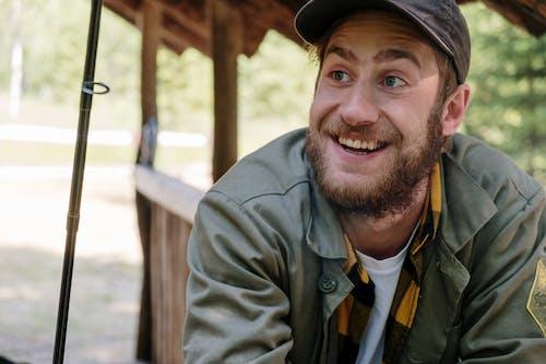 Man in Brown Coat and Black Cap Smiling