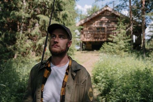 Man in Brown Button Up Shirt Wearing Black Cap