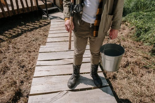 Person in Black Leather Boots Holding Gray Bucket