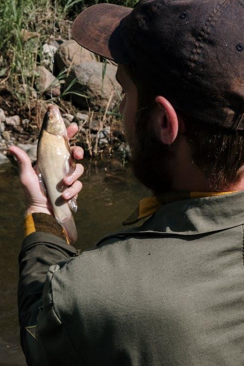 Man in Black Jacket Holding Fish