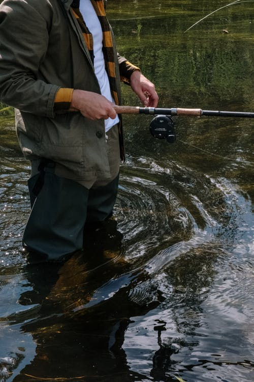 Man in Black Pants and Black Leather Shoes Fishing on River
