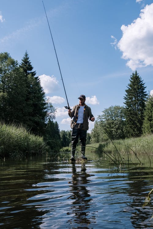Man in White Shirt and Black Pants Fishing on River