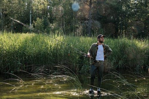 Man in White Shirt Fishing on Lake