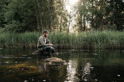 Man in Gray Jacket Sitting on Rock in River