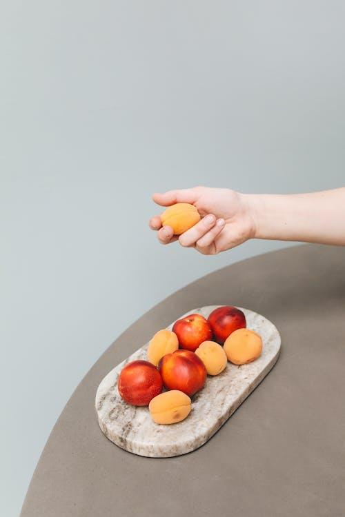 Person Holding Orange Fruit on Gray Tray