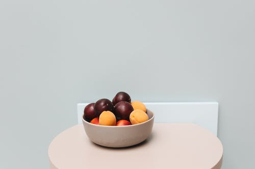 Red and Yellow Fruits on White Ceramic Bowl