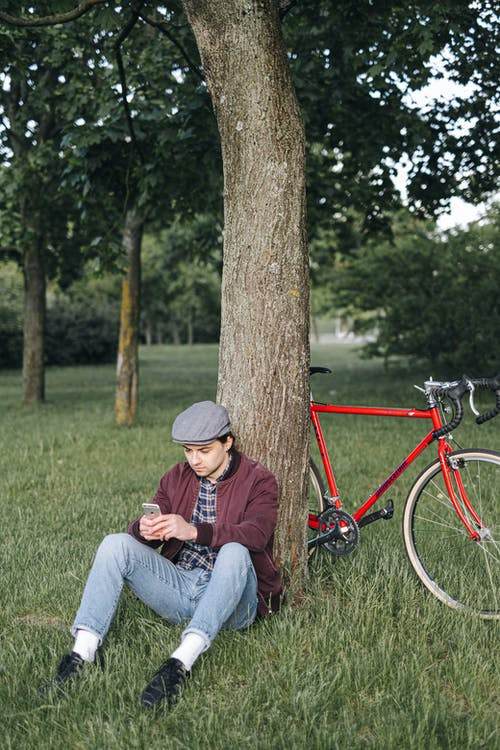 Woman in Brown Hat and Blue Denim Jeans Sitting Beside Red Bicycle