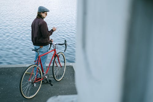 Man in Black Jacket and Blue Denim Jeans Riding Red Bicycle on Road